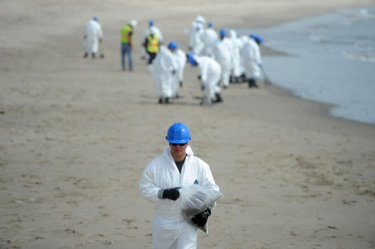 Workers with NRC Environmental Services pick up bits of globs of oil that washed ashore at a Ventura Harbor on May 29, 2015. The oil washed ashore after spilling from a ruptured pipeline at Refugio State Beach in Santa Barbara County.