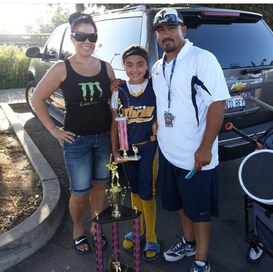 A young Lauren Reynoso, center, poses for a photo with her mother, Elisabeth, and father, Rick. Reynoso's mom passed away in April 2016.