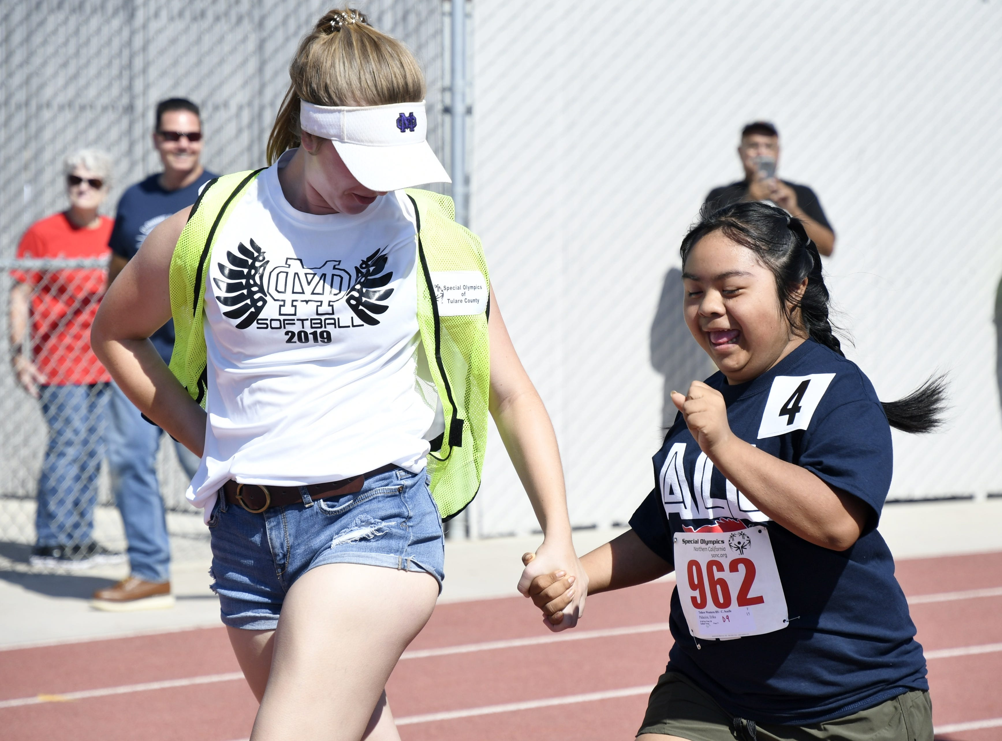 Mission Oak High School student Rayna Souza runs with athlete Erika Palacios, of Tulare Western High School, during the 2019 Tulare County Special Olympics at Bob Mathias Stadium on Friday, April 26, 2019.