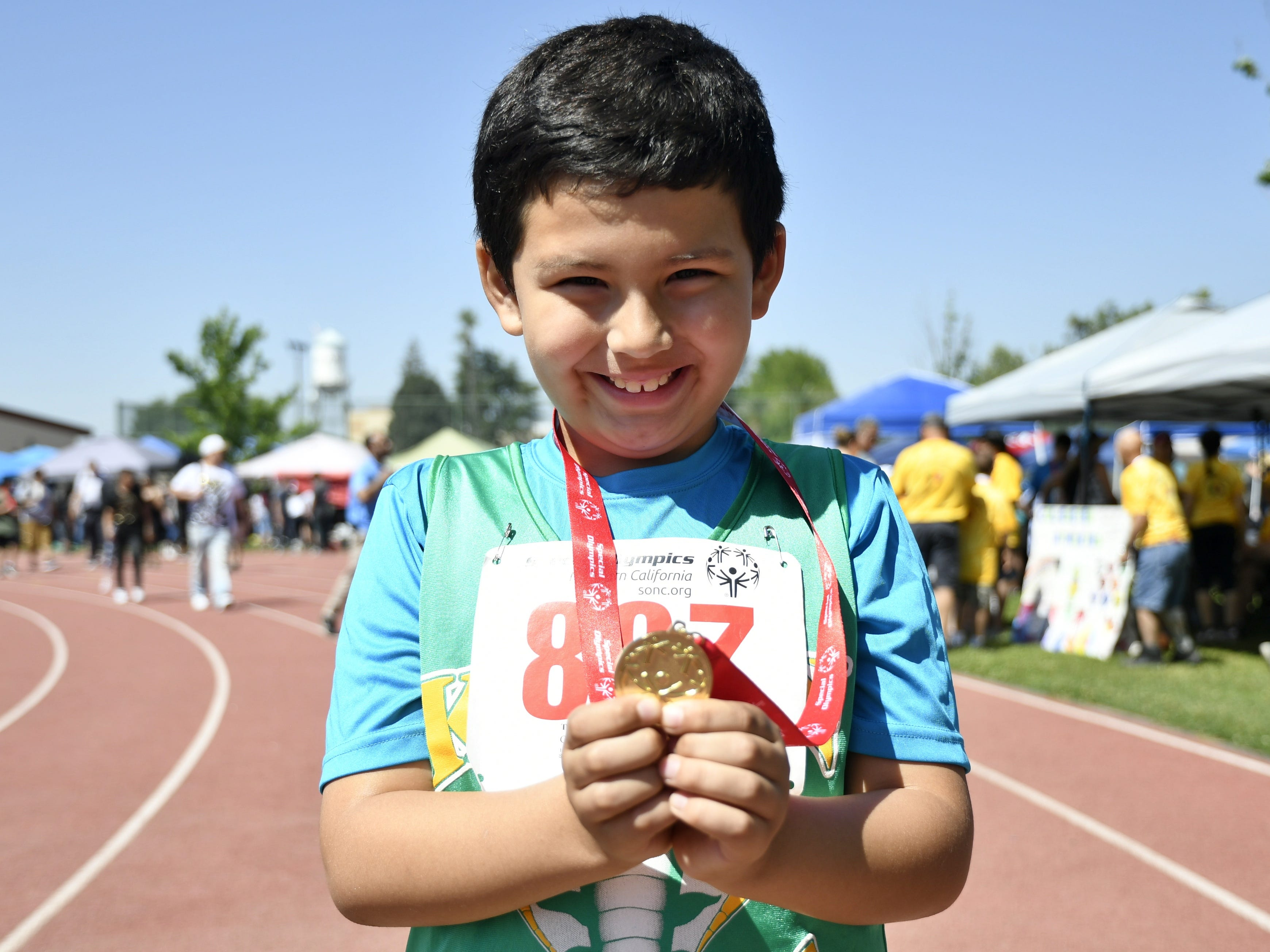 Kohn Elementary student Drew Gamez, 8, shows off his gold medal at the 2019 Tulare County Special Olympics at Bob Mathias Stadium on Friday, April 26, 2019.