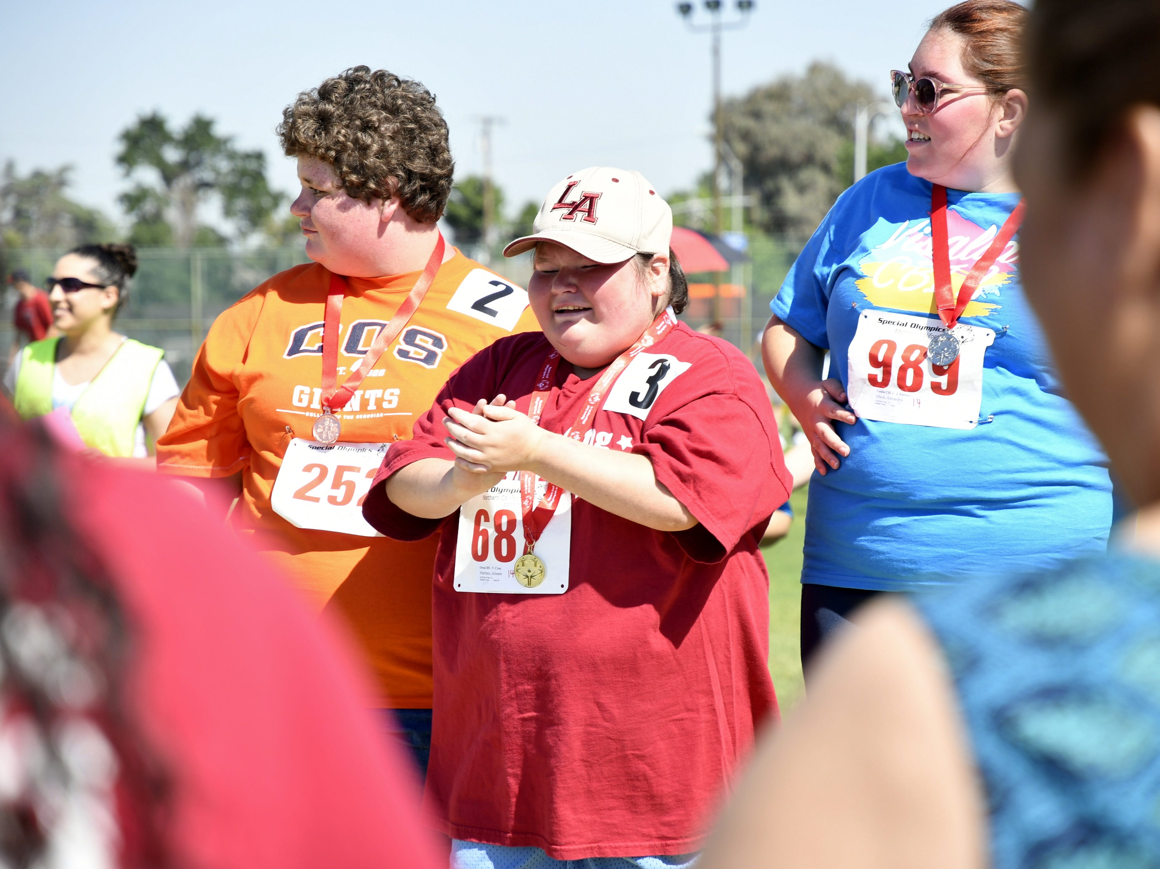 Athletes accept their medals at the 2019 Tulare County Special Olympics at Bob Mathias Stadium on Friday, April 26, 2019.