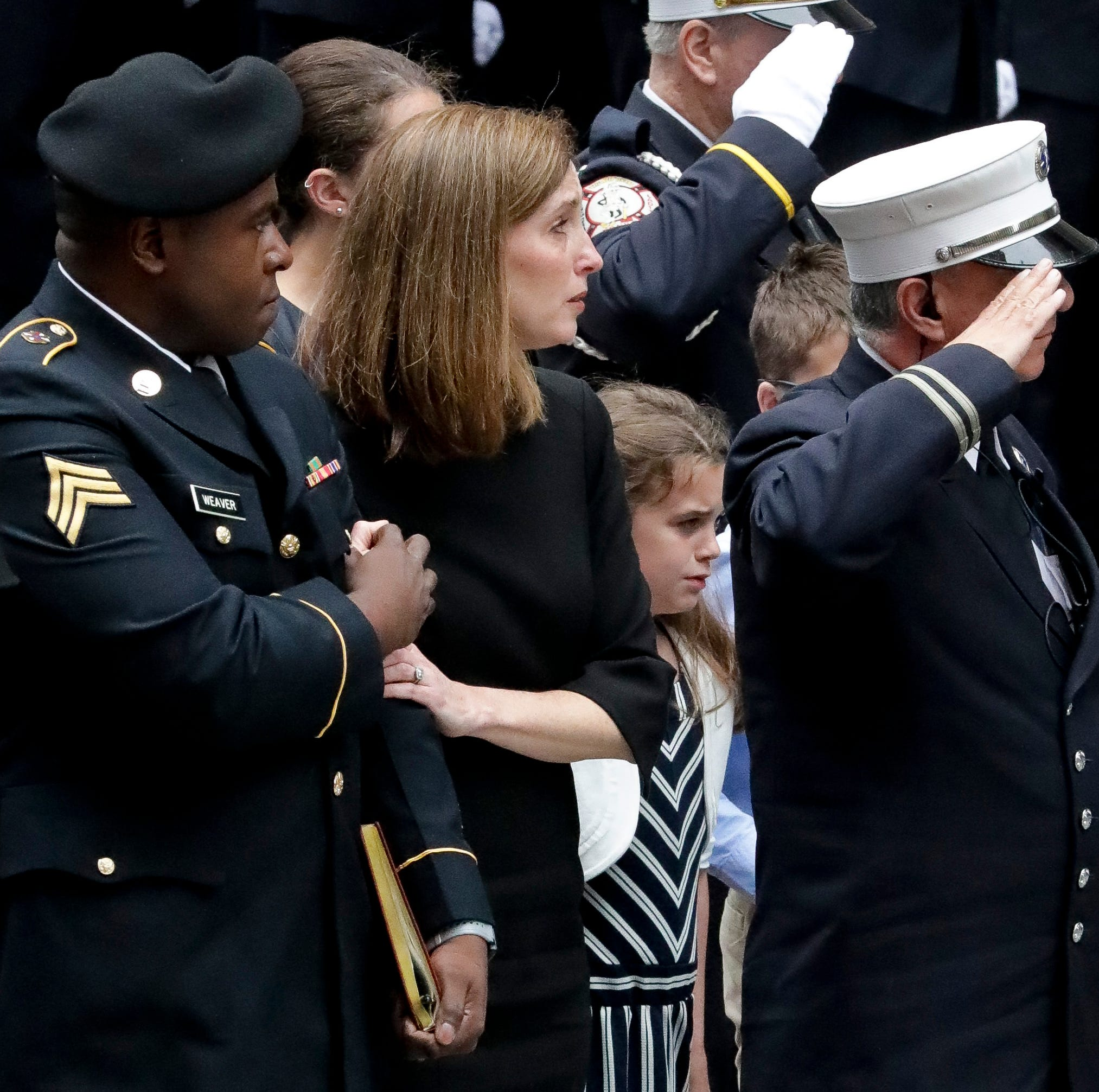 Shannon Slutman, second from left, holds onto a Marine officer as the casket for her husband, U.S. Marine Corps Staff Sergeant and FDNY Firefighter Christopher Slutman, arrives for his funeral service at St. Thomas Episcopal Church, Friday April 26, 2019, in New York. The father of three died April 8 near Bagram Airfield U.S military base in Afghanistan. (AP Photo/Bebeto Matthews)