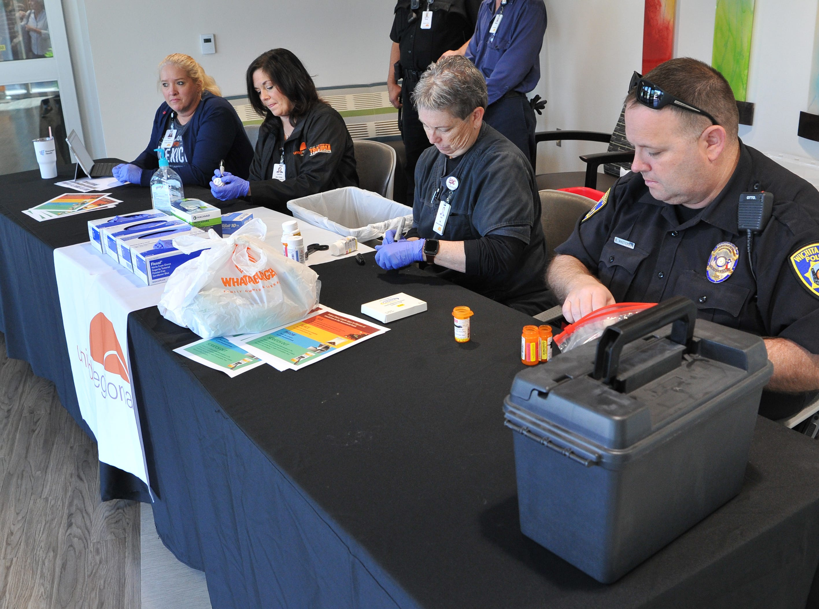 United Regional hospital staff members and Wichita Falls police collect medication during United Regional hospital's and the Wichita Falls Police department's drug take-back event held at the south end of the Emergency Room, Friday afternoon.