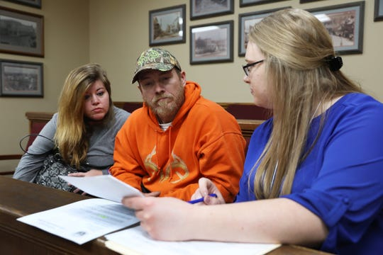 Eddie McElfresh and his fiancee Jenna Nichols talk with Southeastern Ohio Legal Services lawyer Ann Roche during the Don't Hesitate to Reinstate driver's license reinstatement clinic in New Lexington on Friday.