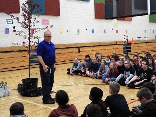 Tom Heading of the Coshocton Tree Commission tell sixth-graders at Coshocton Elementary School what the commission does in the community. Rain prohibited the planting of a prairie fire crab apple tree for Arbor Tree with the students.