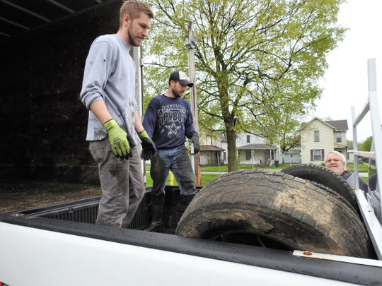 Joe Garrett of the Coshocton City Health Department and Zach Fanning of the Coshocton County Health Department unload tires from a truck Friday at the Coshocton County Fairgrounds for a free scrap tire drive.