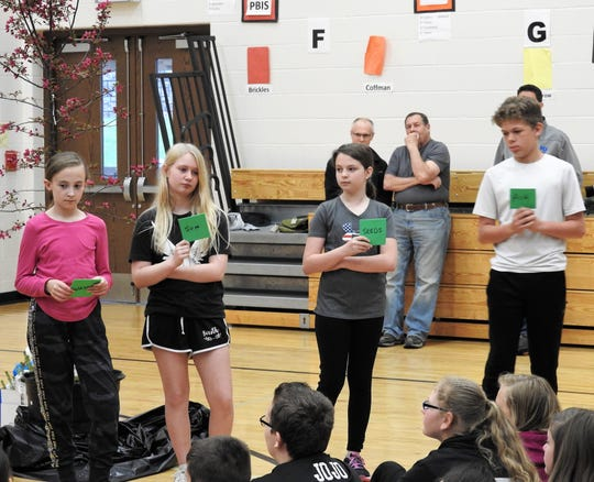 Bristol Mercer, Natalie Strange, Kaitlyn Seitz and Esham Jones-Bennett hold up signs on what trees need to grow such as water, sun, seeds and air during an assembly for Arbor Day Friday at Coshocton Elementary School.