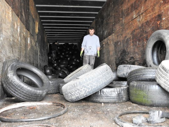 Zach Fanning of the Coshocton County Health Department and Joe Garrett of the Coshocton City Health department organize tires in a trailer Friday at the Coshocton County Fairgrounds for a free scrap tire drive. They were looking to take between 1,200 and 1,500 passenger tires for recycling.