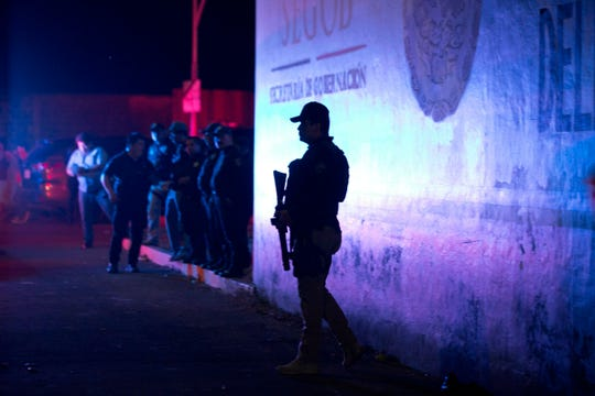 A Federal Police officer stands guard outside an immigration detention center in Tapachula, Chiapas state, Mexico, late Thursday, April 25, 2019. A large group of mainly Cuban migrants escaped on foot from the immigration detention center on Mexico's southern border in the largest mass escape in recent memory. Later, about half of the group returned voluntarily.