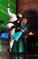 Christian Wilkins (Clemson) celebrates with NFL commissioner Roger Goodell after he was selected as the number thirteen overall pick to the Miami Dolphins  in the first round of the 2019 NFL draft.