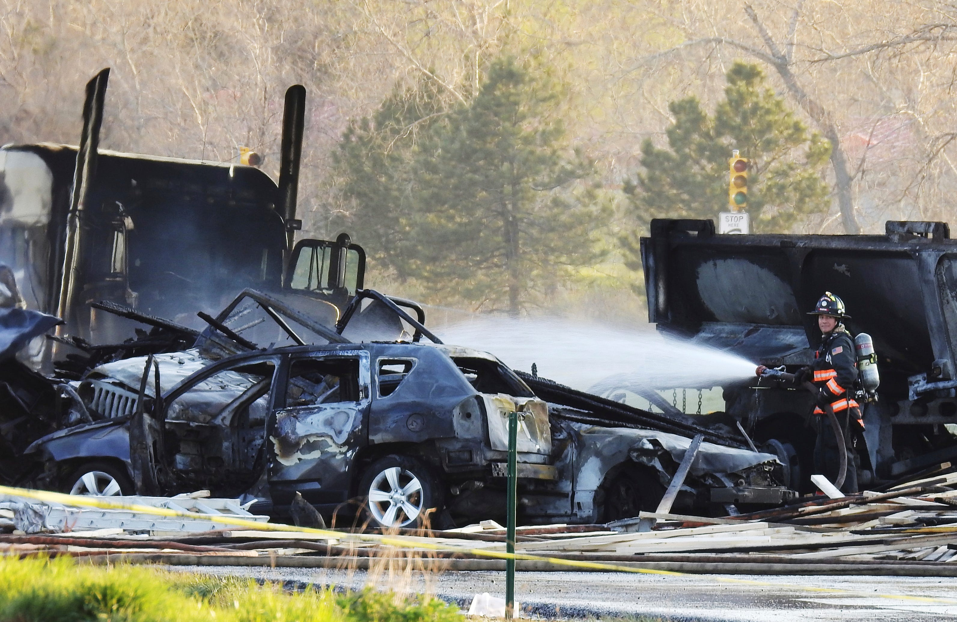 A firefighter sprays water on the wreckage in Lakewood, Colo., after a deadly collision on Interstate 70 near the Colorado Mills Parkway, April 25, 2019.