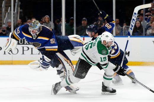Second round: Jordan Binnington is upended by Stars left wing Blake Comeau after the Blues goalie left the net to clear a loose puck in Game 1.