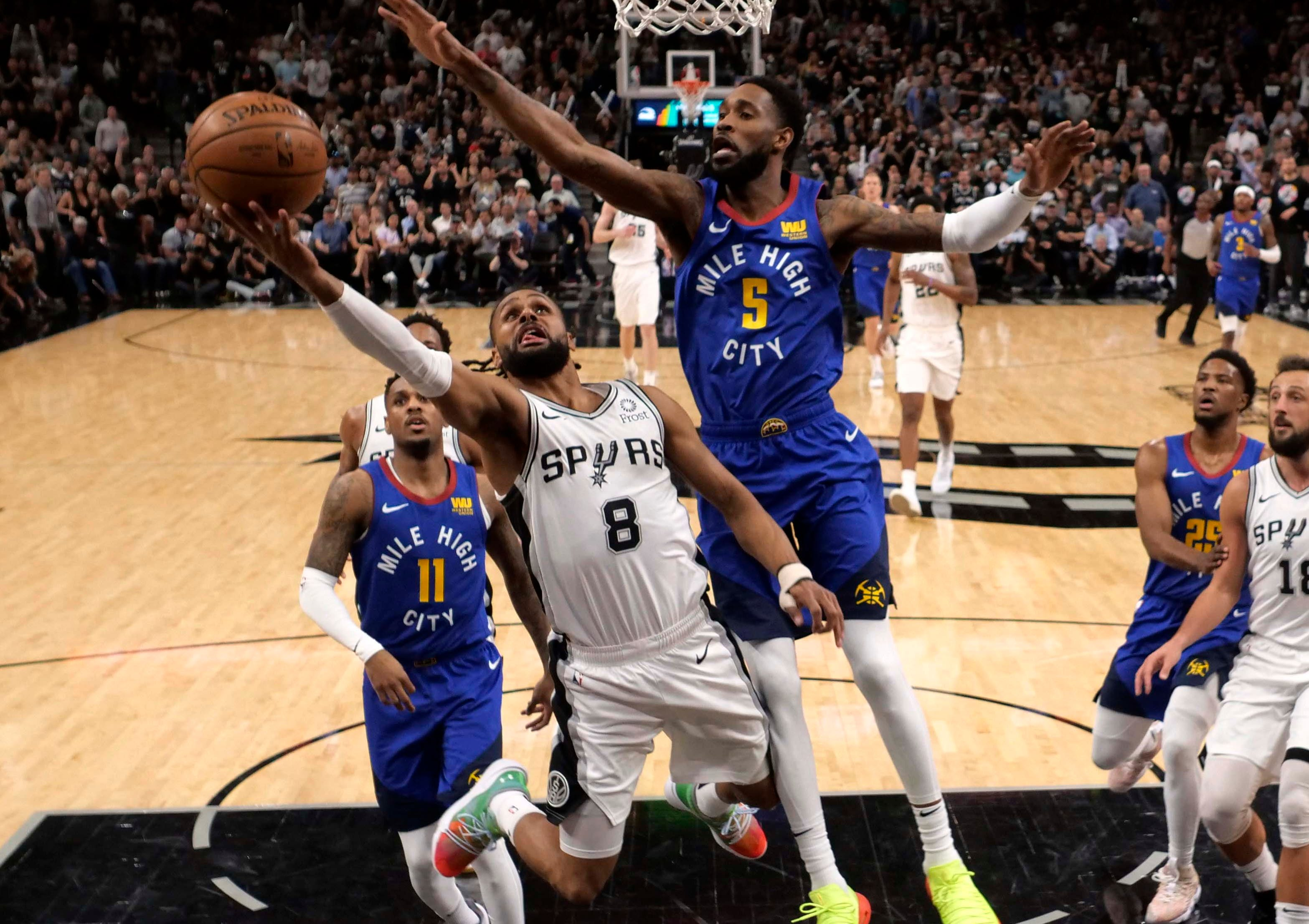April 25: Spurs guard Patty Mills (8) drives to the bucket against Nuggets defender Will Barton (5) during Game 6 in San Antonio.