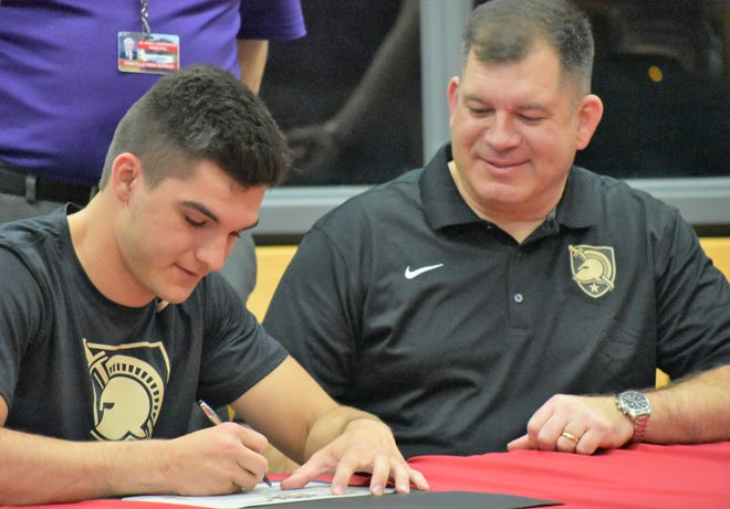 Pineville senior quarterback Ben West (left) signs a letter of intent to play sprint football for Army as his dad Stuart looks on during a ceremony in the school's library Friday afternoon.