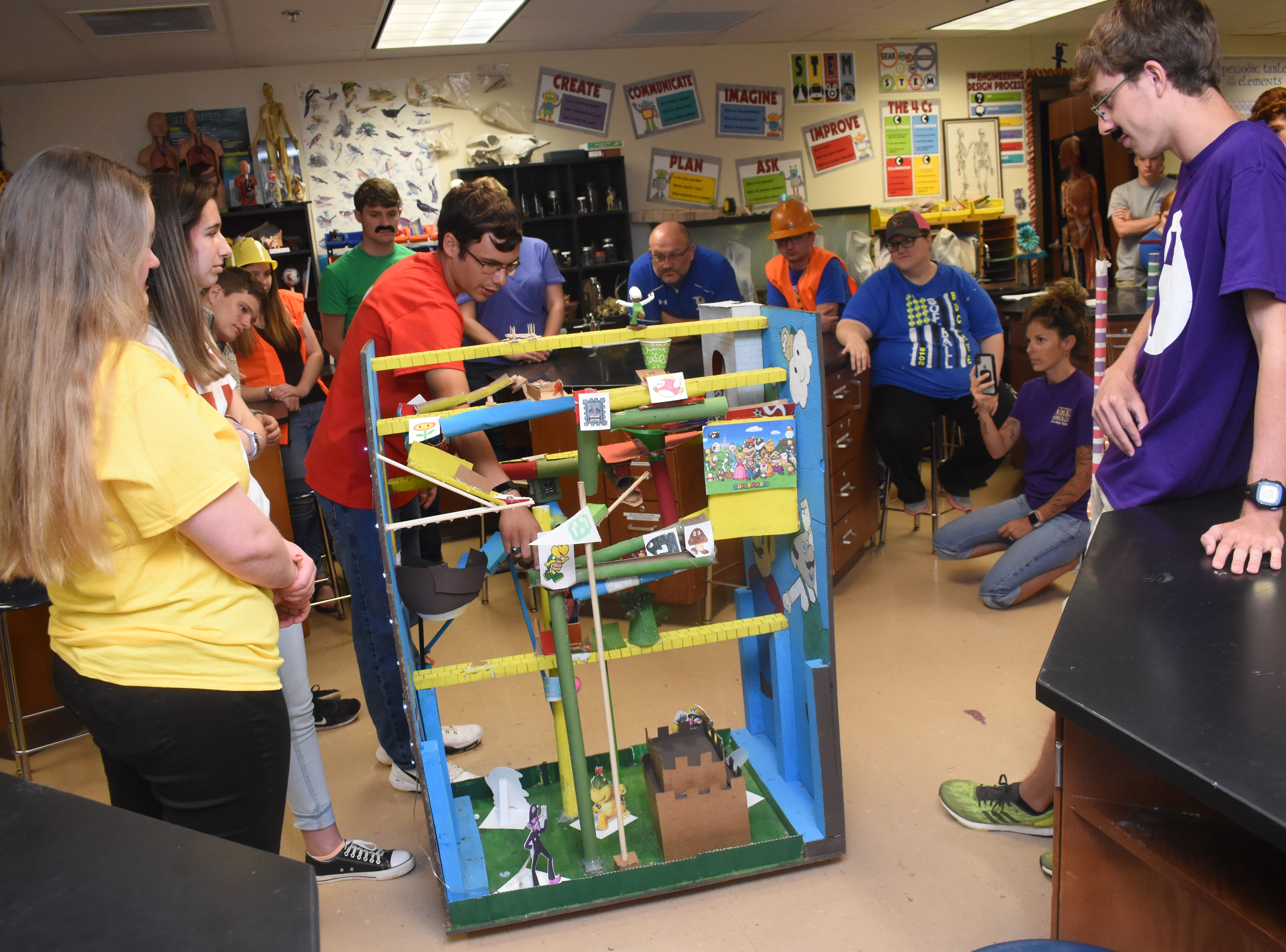 Buckeye High School senior Evan Norris (in red shirt) explains to judges how the Rube Goldberg machine he and his group created works. The theme for their machine was based on the video game Super Mario Bros. The end result was for the machine to raise a flag. Students in Lacey Hoosier's science class applied S.T.E.M. principles (Science. Technology. Engineering. Math.) in creating Rube Goldberg machines. The Website www.rubegoldberg.com says Rube Goldberg machines are machines designed to do simple tasks in a complex manner. For example, a simple task for one of the groups in the class was getting the machine to put an Alka-Seltzer tablet in a cup of water. The machines were designed by inventor and cartoonist Rube Goldberg.