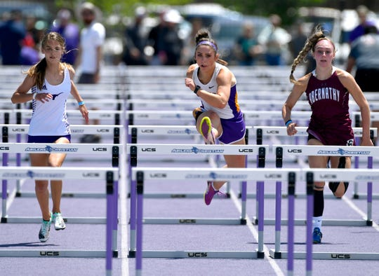 Merkel's Kaydi Pursley (center) runs to win the girls 100 meter hurdles during Saturday's Region 1-3A track meet.