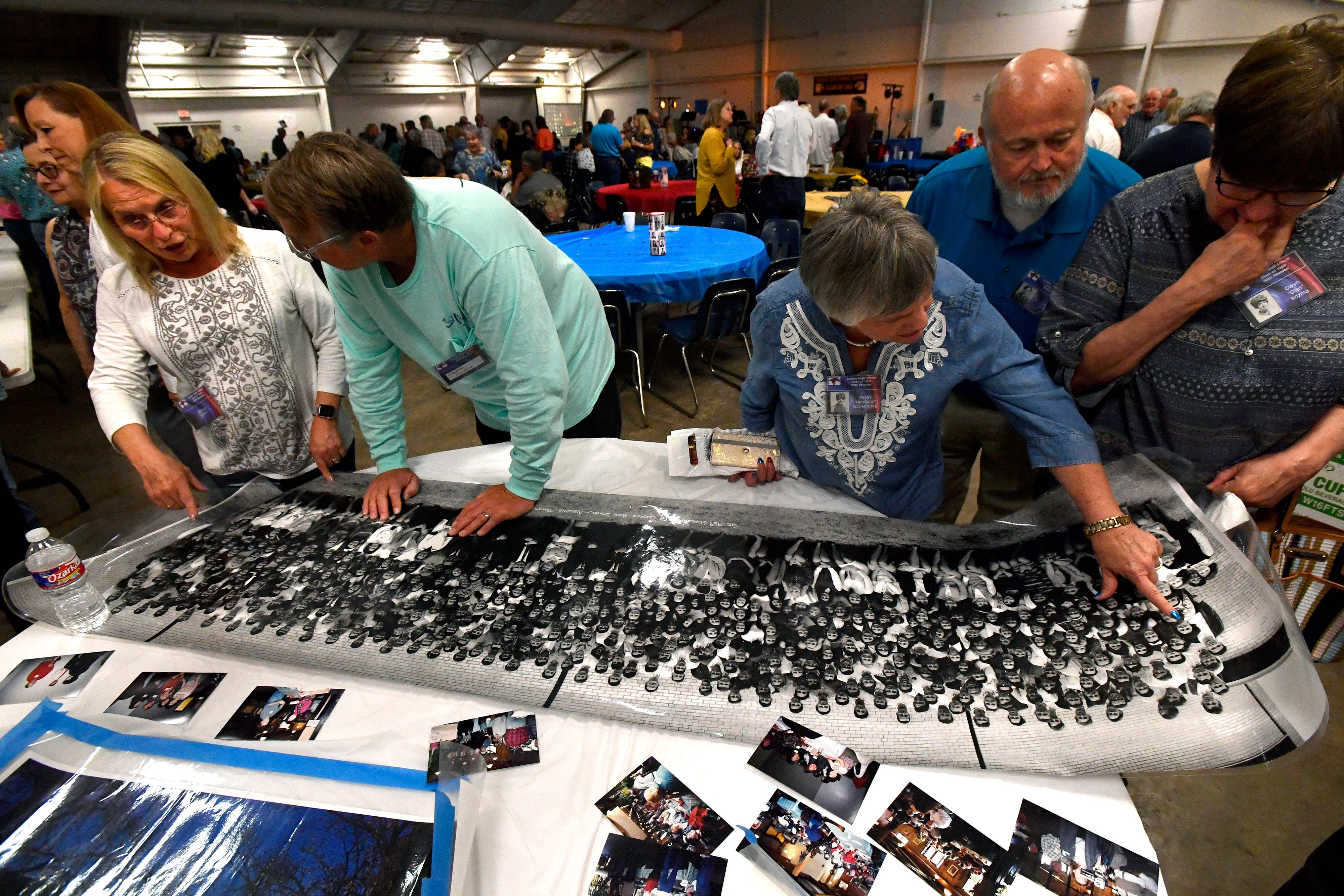 Attendees look over a class portrait of the Cooper High School Class of 1969 during Friday's reunion of Cooper and Abilene high schools from that year at the Taylor County Expo Center.