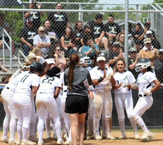 Abilene High's Alyssa Washington, right, comes home to a party after hitting a two-run home run to give her team a 16-0 lead in the second inning April 27 against Arlington High. She walked and scored earlier in Abilene's 15-run outburst.