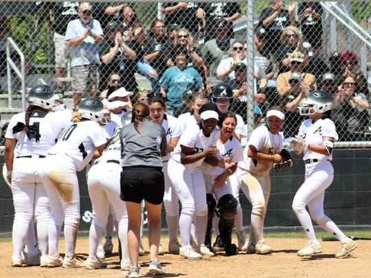 Abilene High's Aubrianna Salazar, right, joins the celebration already in progress at home plate after hitting a 3-run home run in the second inning Saturday at the AHS ballpark. The blast game AHS a 10-0 lead against Arlington High in the Class 6A bi-district series.