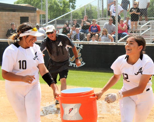 Kaylen Washington (10) and Aubrianna Salazar (12) scurry back to the dugout with Coach Jim Reese in pursuit after the Abilene High players drenched him after Saturday's 18-0 win over Arlington High that advanced their team in the Class 6A state softball playoffs.