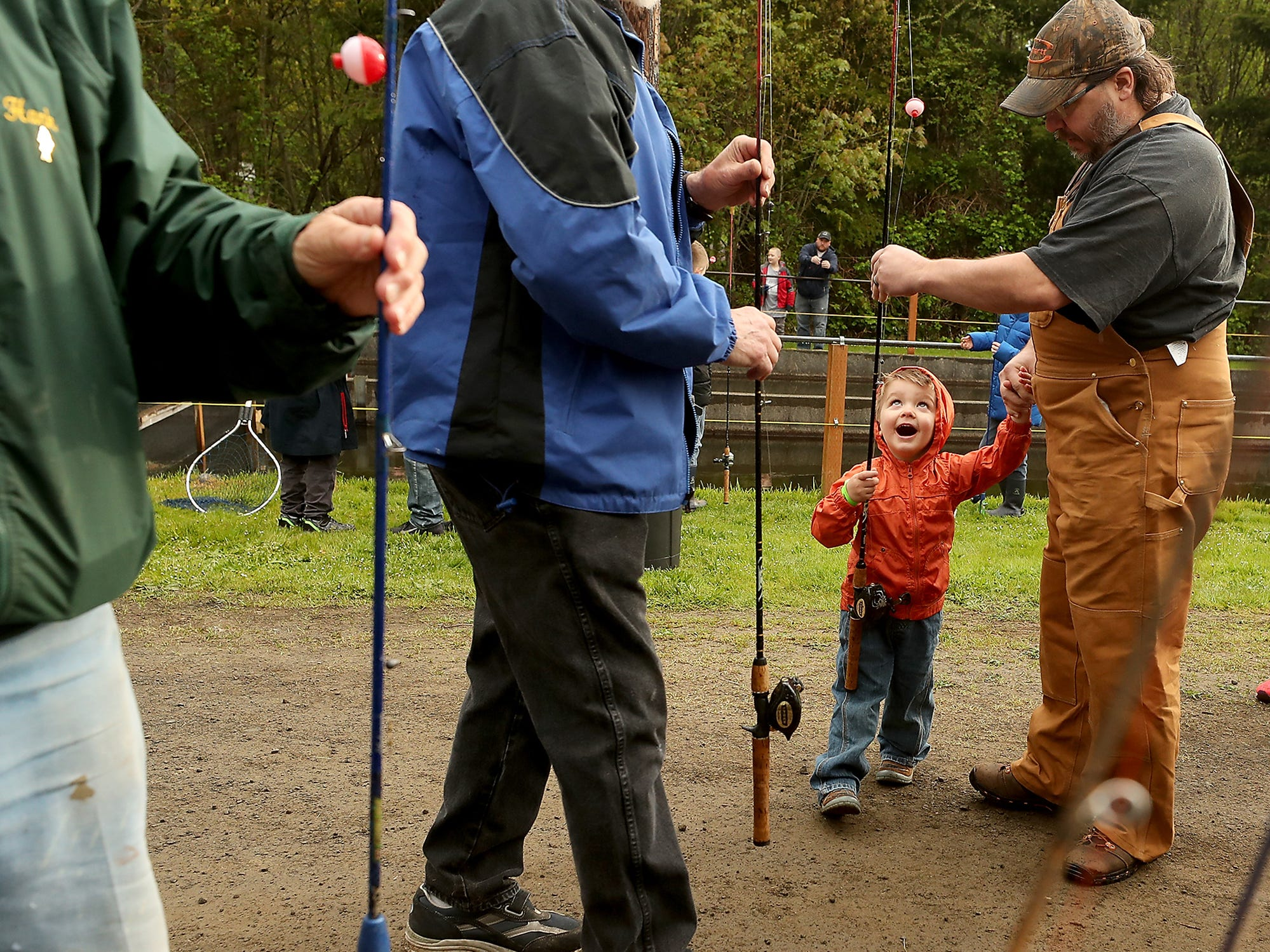 Three-year-old Owen Rasmussen is in awe as his father Eric hands him his very own fishing rod to use during the Kids Fishing Party at Jarstad Park in Gorst on Saturday, April 27, 2019.  The Kitsap Poggie Club - who host the event every year on the opening day of trout season - stocks the hatchery raceway with trout and provides fishing gear, bait, snacks and fish cleaning to those taking part in the fishing day of fun.