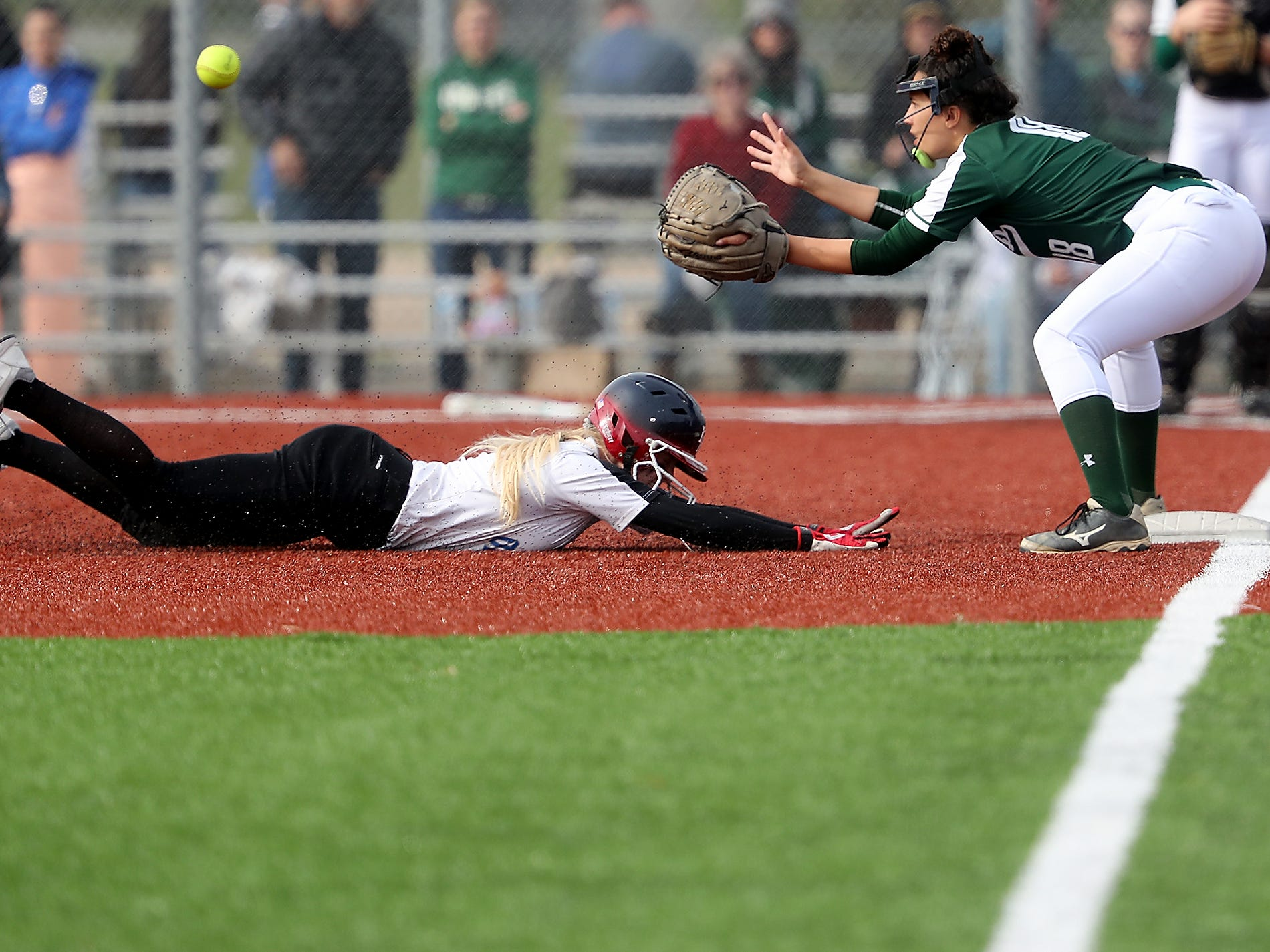 Olympic's Molly Gates slides into third ahead of the catch by Port Angeles's Lucah Folden during their game on Friday, April 26, 2019. Gates was safe on the play.