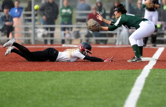Olympic's Molly Gates slides into third ahead of the catch by Port Angeles' Lucah Folden during an Olympic League 2A softball game on Friday, April 26, 2019. Gates hit for the cycle during the game, a 10-6 victory for Port Angeles.