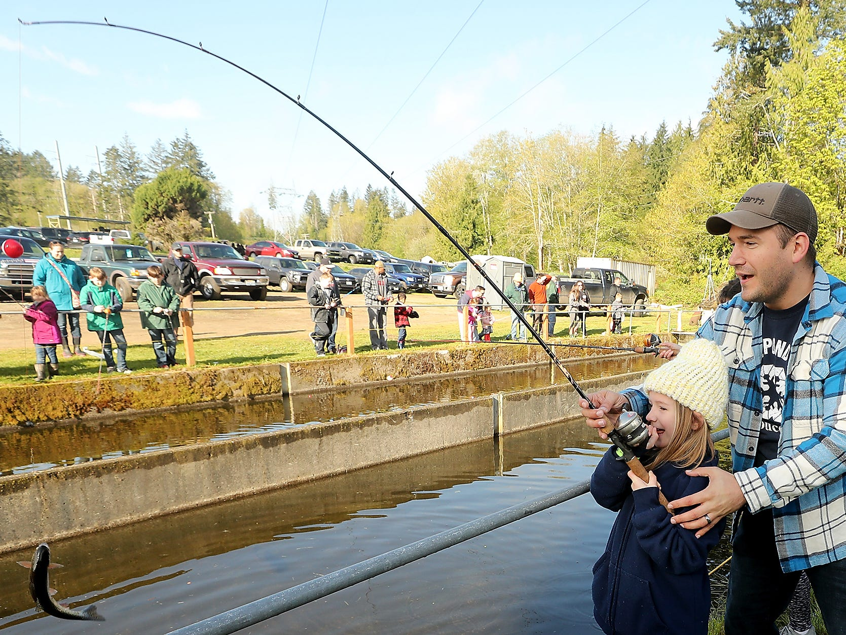Brett Palmer helps his daughter Stella, 6, land her catch during the Kids Fishing Party at Jarstad Park in Gorst on Saturday, April 27, 2019.