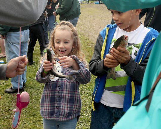 Liliana Poirier, 6, (left) and cousin Maximus Zuniga , 9, hold their freshly caught fish while their family snpas photos of them during the Kids Fishing Party at Jarstad Park in Gorst on Saturday, April 27, 2019.