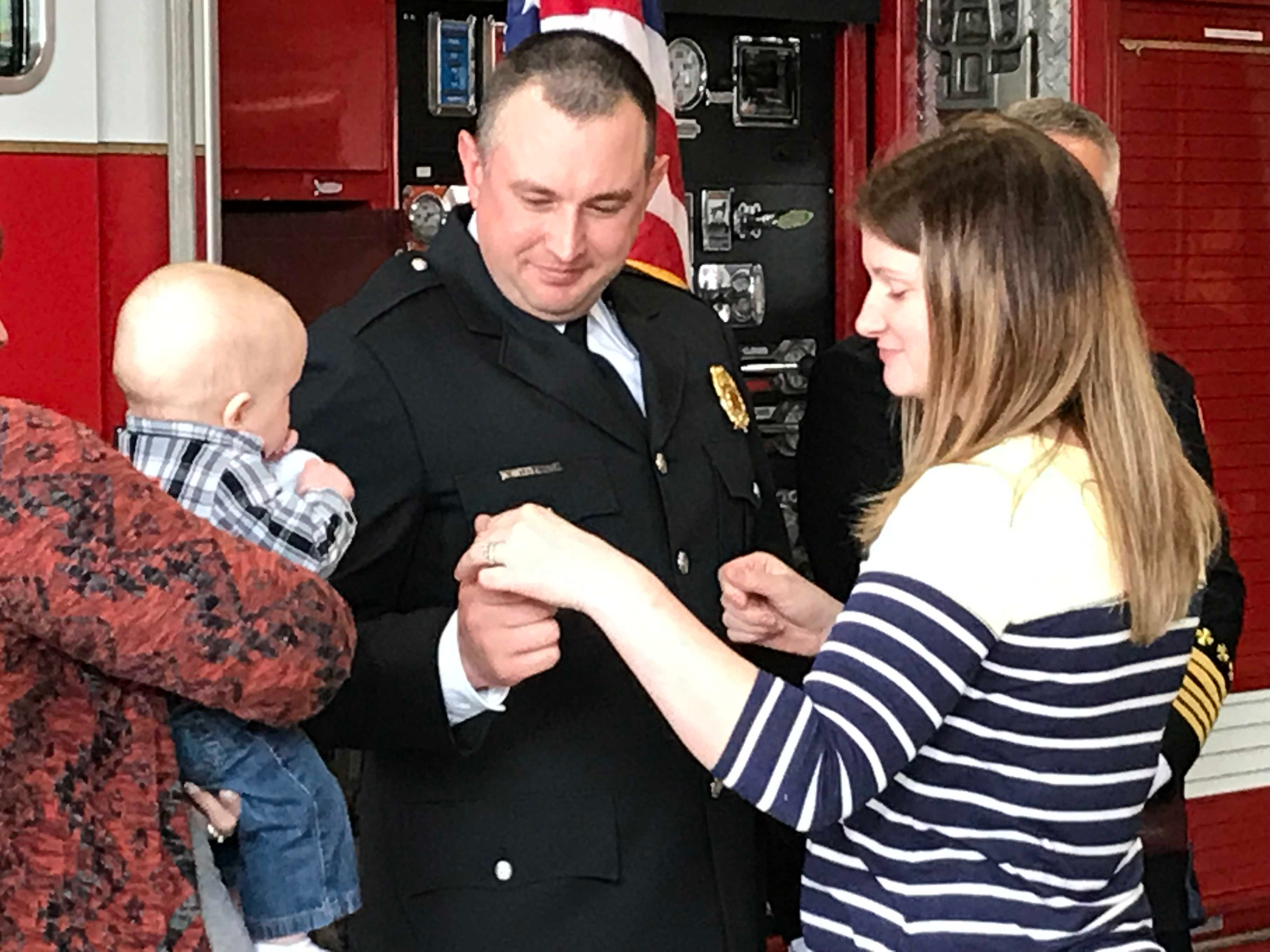 New Chillicothe Fire Lt. Nick Mathias smiles as his wife prepares to affix another new pin to his jacket during a special promotion swearing in and pinning ceremony on Friday, April 26, 2019.