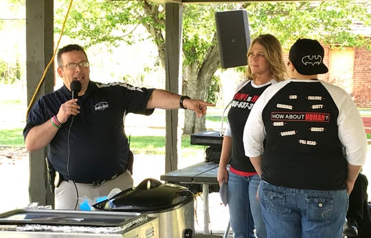 "Chillicothe Police Officer Bud Lytle points out the shirts worn by Laken Woods, left, and Vanessa Escamilla, who are both certified peer recovery supporters, during the Stop the Stigma Rally at Southern Playground on Saturday, April 27, 2019. The shirts say ""Hope is Here"" with the phone number 740-637-3748 on the front while the back displays crossed out words like ""liar"" and ""pill head"" surrounding the alternative, ""How about human?"""