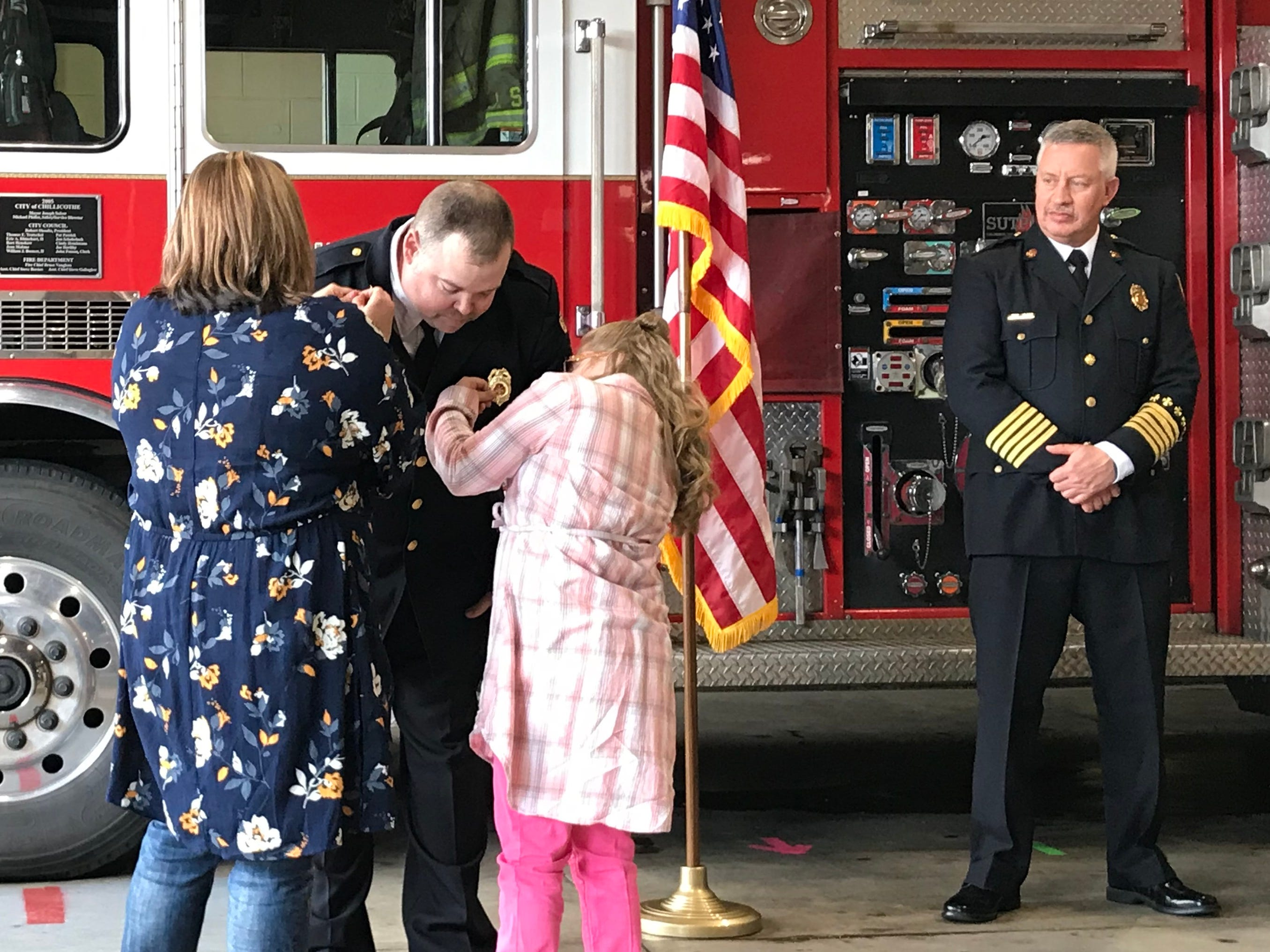 Chillicothe Fire Department's new Assistant Chief Aaron Knotts bends down as his wife Belinda and 10-year-old daughter Sara affix his new pins while Chief Jeff Creeds watches during a pinning and promotion ceremony on Friday, April 26, 2019, at Station 1.