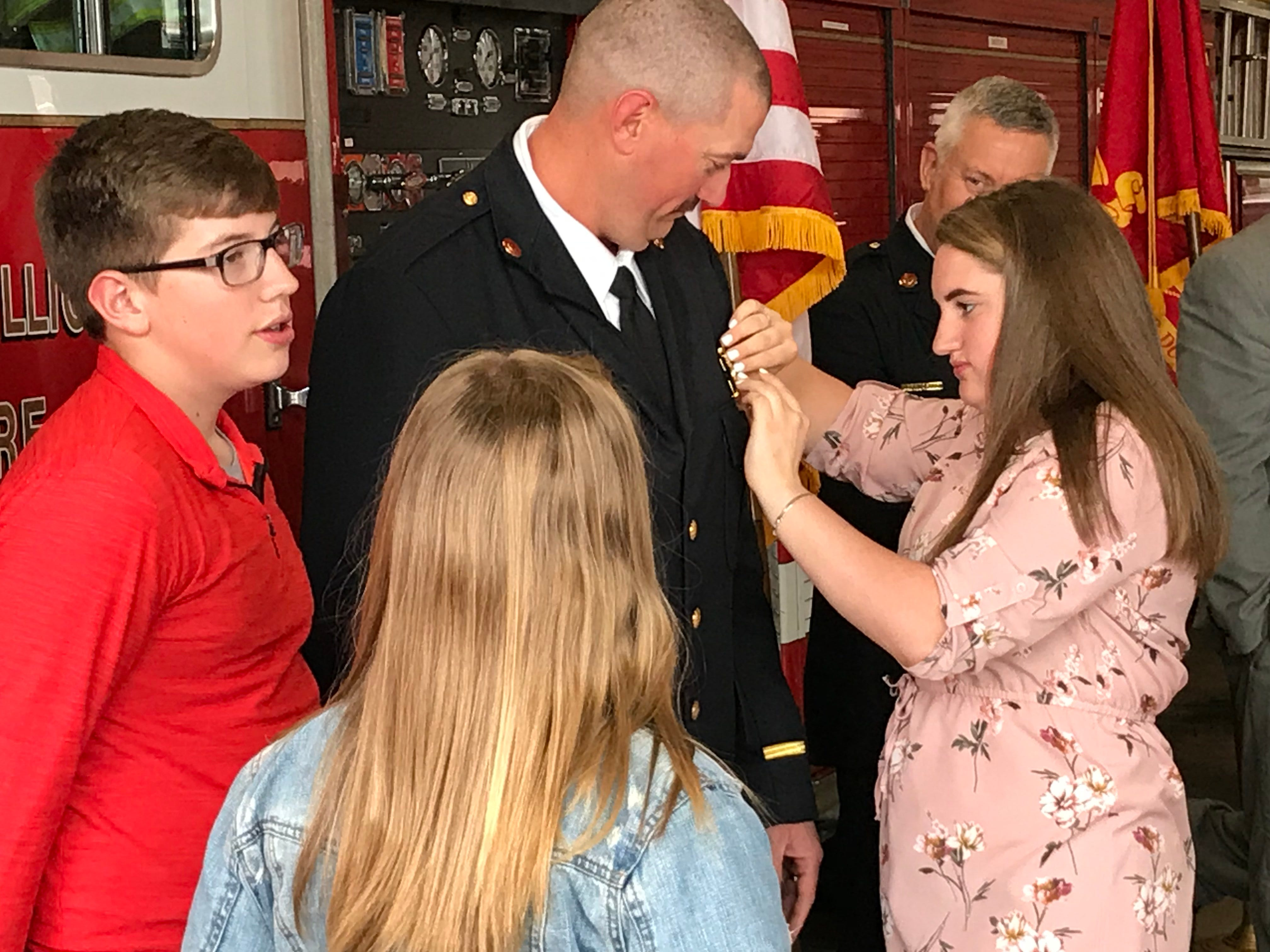Chillicothe Fire Department's newest captain Ryan Wade watches as one of his daughters affix a pin to his jacket during a special swearing in and pinning ceremony for his promotion on Friday, April 26, 2019.