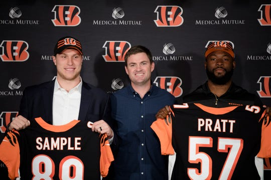 From left, Bengals tide end Drew Sample, 2nd round draft pick from the University of Washington, Bengals head coach Zac Taylor and Bengals linebacker Germaine Pratt, from 3rd round draft pick from North Carolina State University, hold their jerseys during a press conference on Saturday, April 27, 2019, at Paul Brown Stadium in Cincinnati.