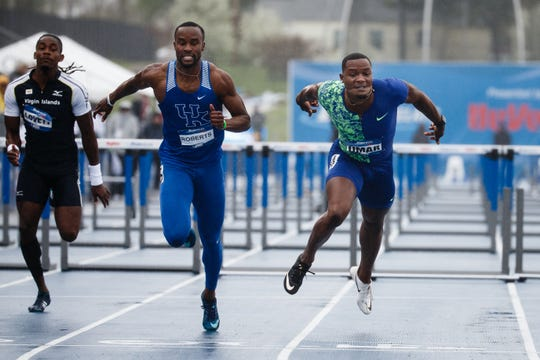 Daniel Roberts from Kentucky, center, crosses the line a hundredth of a second before Omar McLeod during their men's elite 110 meter hurdle race Saturday at a rainy Drake Stadium.