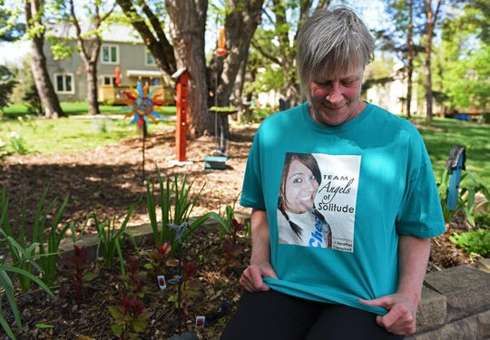 Vicki Campbell, 58, sits for a portrait outside her Urbandale home on Friday, April 26, 2019, as she looks down at a photo of her daughter, Heather Campbell, who was murdered in 2010. Vicki is participating in her 10th walk for Autism Speaks on Saturday in memory of her daughter.