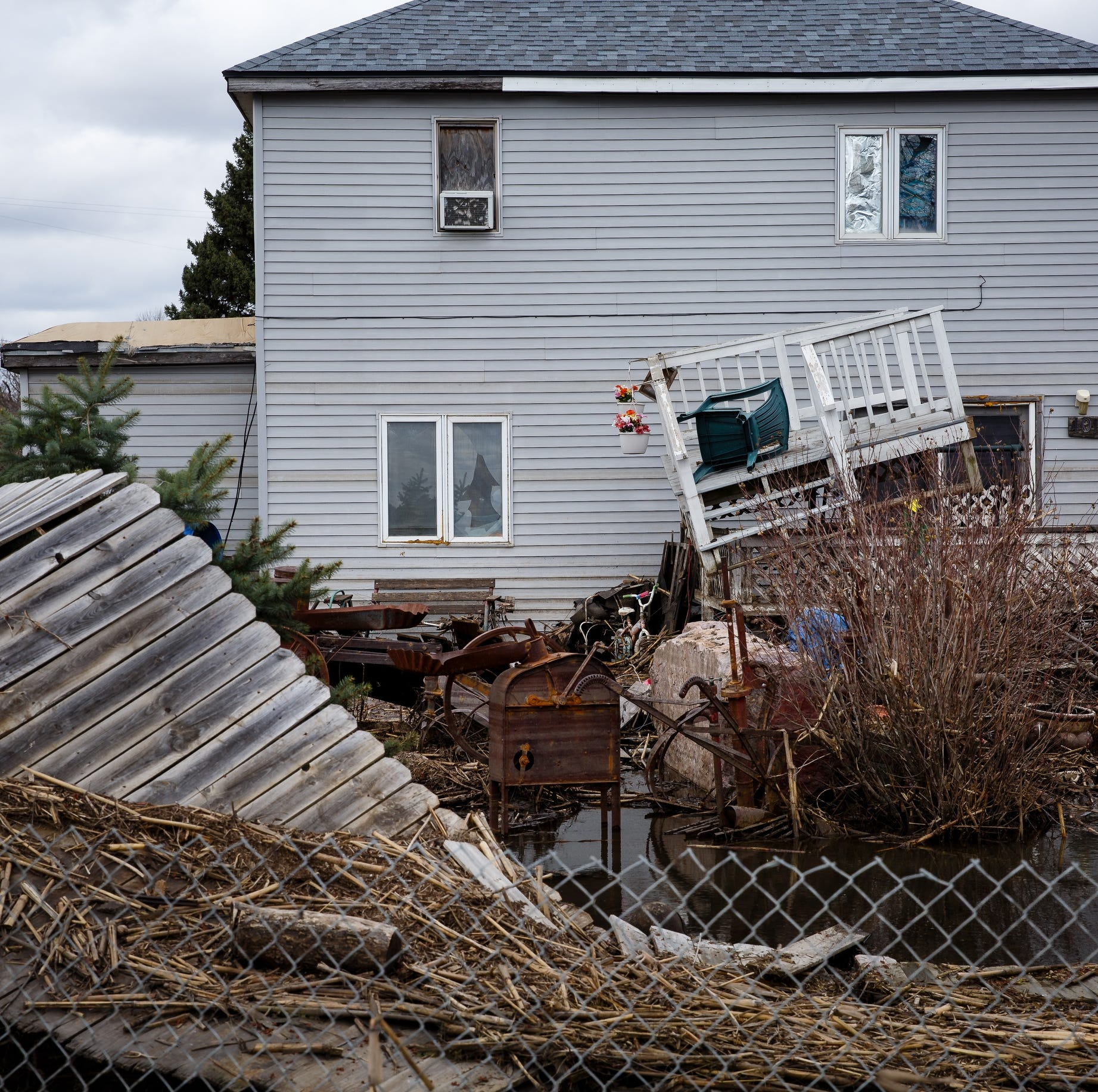 Decks, fences and cornstalks litter the yard of a home leftover from the floodwaters on Friday, April 12, 2019, in Pacific Junction.