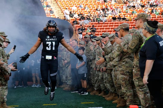 Hawaii linebacker Jahlani Tavai runs through a group of Army soldiers before the start of a game against Navy at Aloha Stadium, Sept. 1, 2018.