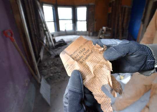 Audra's life partner, Daniel Land, of Detroit, shows off this 1930s article from The Detroit News that he found in the space between the floor boards.