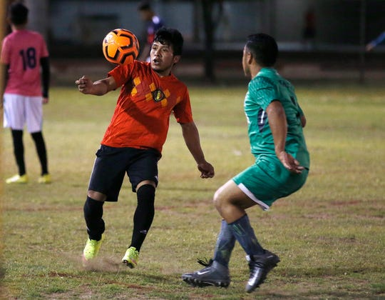 Adelfo Guillermo Martin Perez, 24, left, an arrival in the United States for three months and originally from Guatemala, controls the ball at a Maya Chapin soccer league game at a soccer league game Wednesday, April 17, 2019, in Phoenix. (AP Photo/Ross D. Franklin)