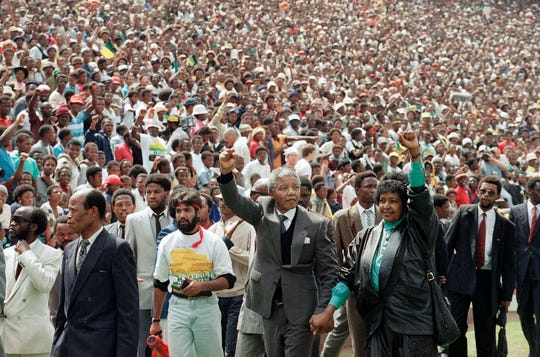 Nelson Mandela and Winnie Mandela give black power salutes Feb. 13. 1990, as they enter Soccer City stadium in the Soweto township of Johannesburg, South Africa