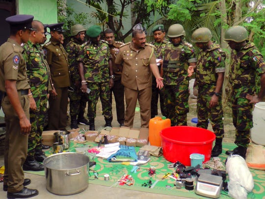Sri Lankan police and army officers display bomb making materials recovered from a hideout of militants after Friday's gunbattle in Kalmunai, in eastern Sri Lanka, Saturday, April 27, 2019.