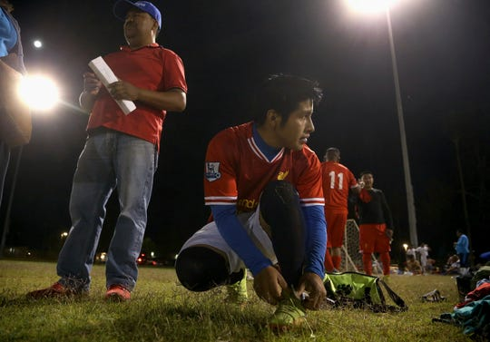 Pedro Chilel, 21, abandoned by his parents in Guatemala before he traveled alone to the United States at age 17, ties his shoes before his Maya Chapin soccer league game Wednesday, April 17, 2019, in Phoenix.