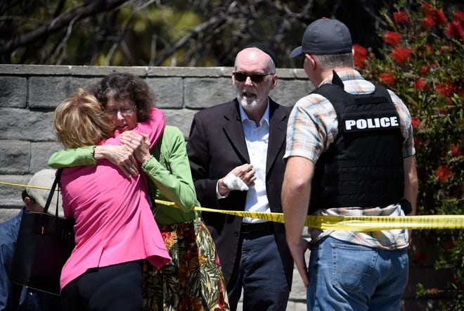 Two people hug as another talks to a San Diego County Sheriff's deputy outside of the Chabad of Poway Synagogue Saturday, April 27, 2019, in Poway, Calif.