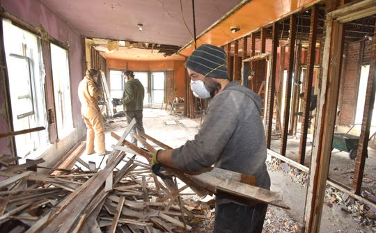 Audra's work partner, Aaron Timlin, of Detroit, goes through lathe wood on the second floor of the home in Detroit's northwest Goldberg neighborhood.