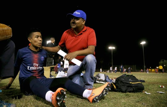 Antonio Velasquez, right, a pastor and director of the Maya Chapin soccer league, talks with player William Sebastian, 16, left, during a break in a soccer league game April 17, 2019, in Phoenix.