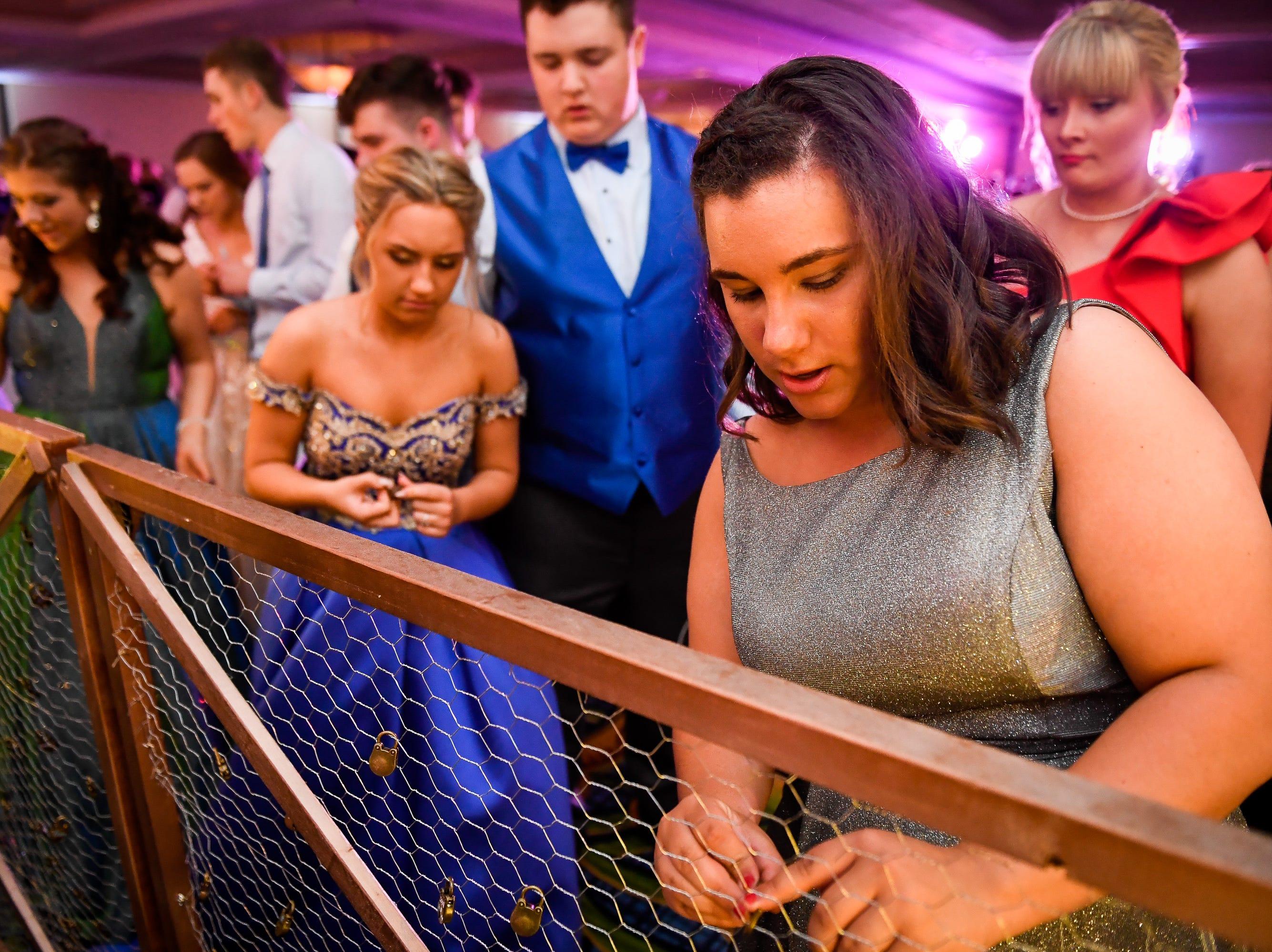 Leah Beach, right, unlocks a souvenir lock at the Tecumseh High School prom held at the Airport Holiday Inn Friday, April 26, 2019.