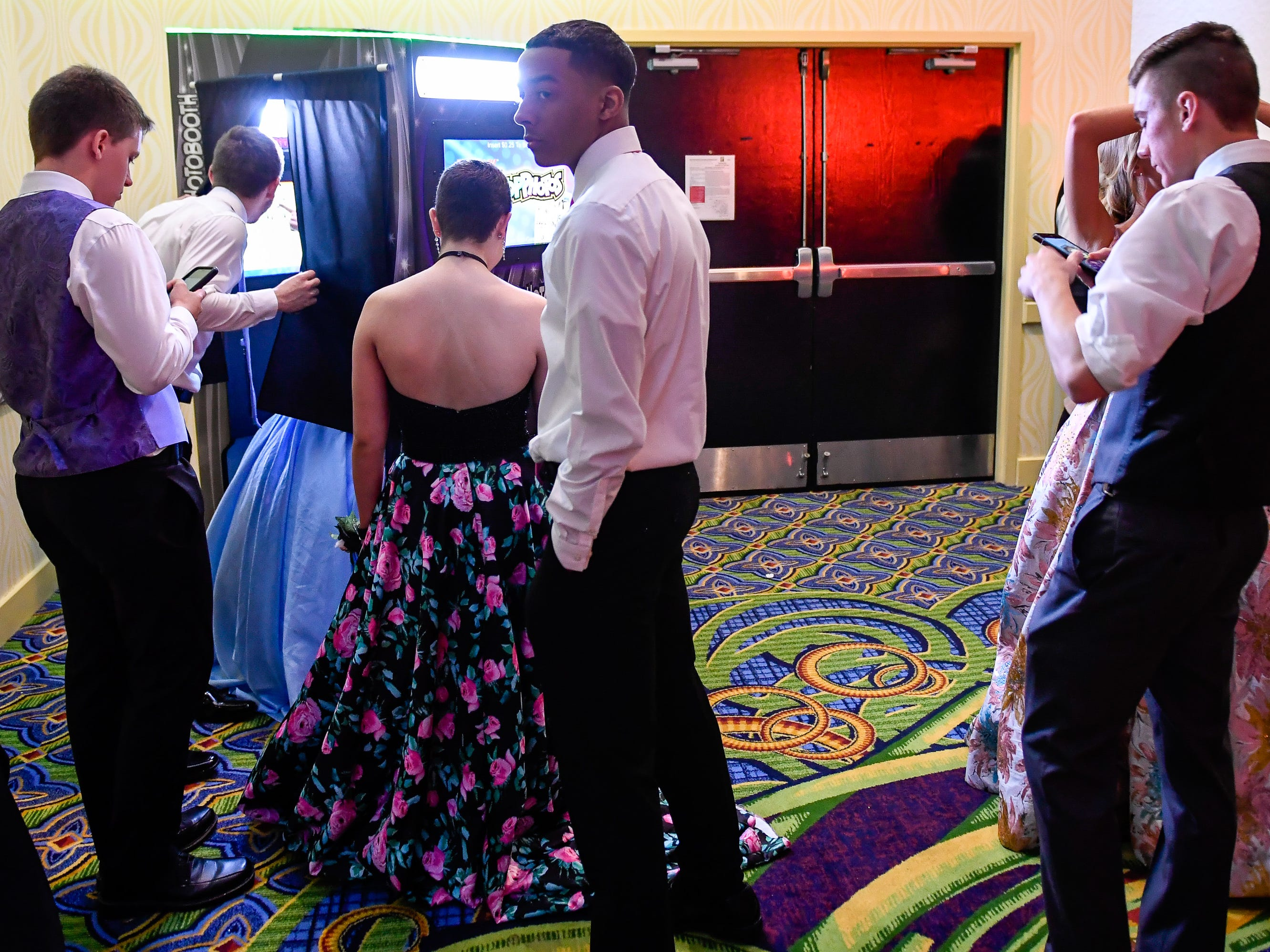Lining up at the photo booth at the Tecumseh High School prom held at the Airport Holiday Inn Friday, April 26, 2019.