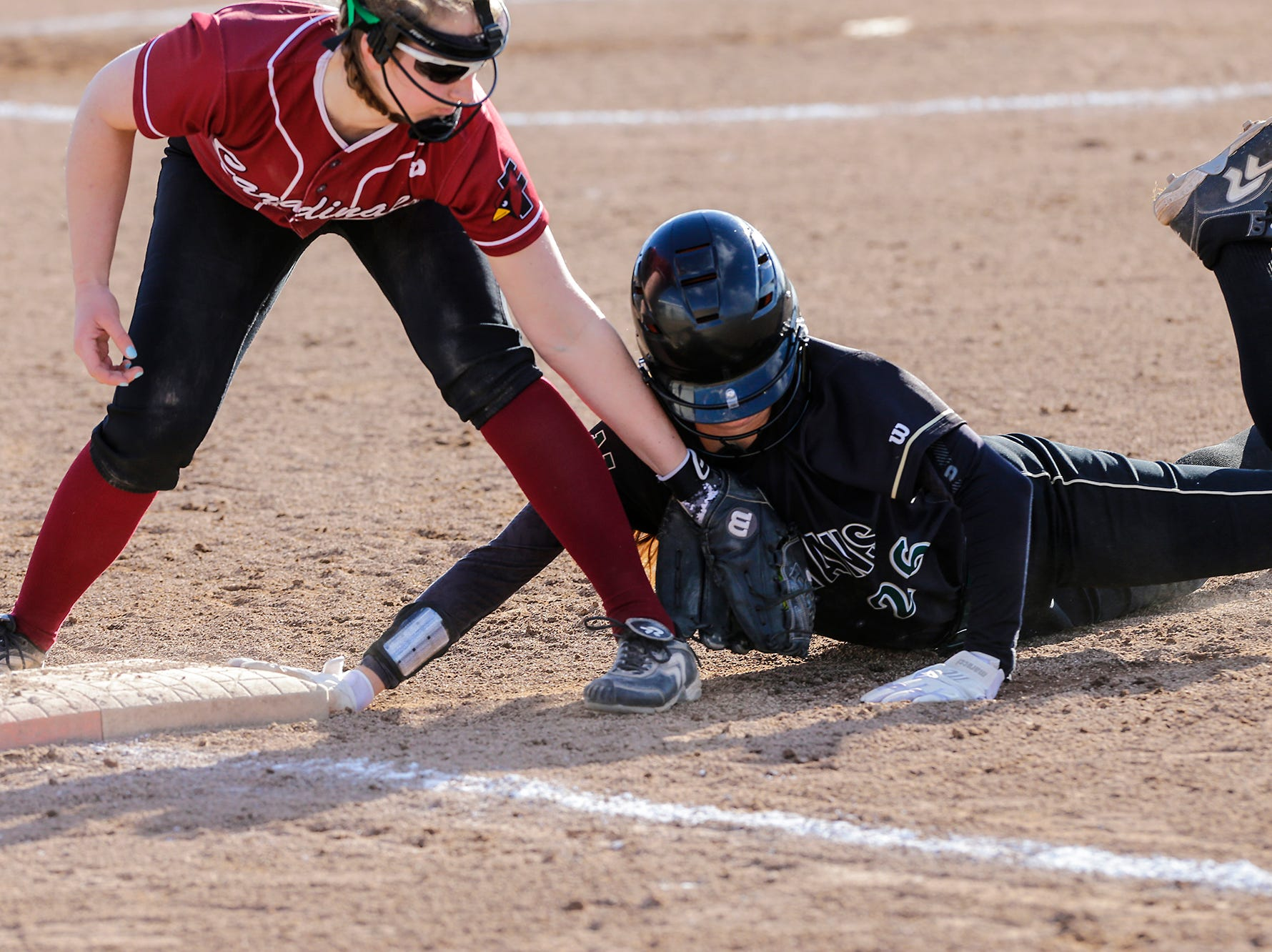 Fond du Lac High School softball's Kellie Hierl (5) attempts to tag Oshkosh North High School's Syd Supple (26) as she dives back to first base during their game Friday, April 26, 2019 in Fond du Lac, Wis. Doug Raflik/USA TODAY NETWORK-Wisconsin