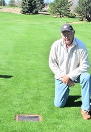 Jim Eyberg poses next to the plaque in the ninth fairway at Ptarmigan Country Club, commemorating his lifetime achievement of shooting an eagle on every hole on the course in Fort Collins, Colo.